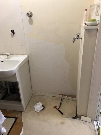 洗濯機を取り外して、壁紙や床のクッションフロア、巾木を剥がしているところ