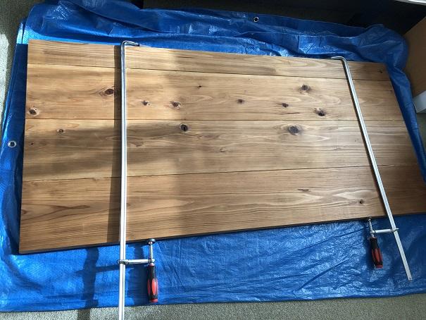 FLEXISPOT電動昇降式スタンディングデスクの天板にする杉カフェ板に塗装して1日乾燥、接着しているところ