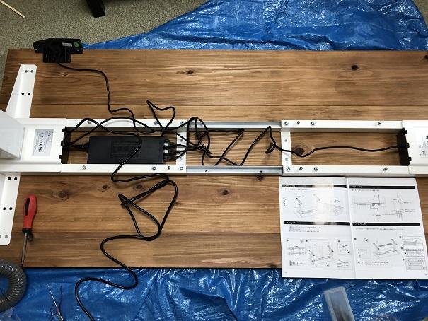 FLEXISPOT電動昇降式スタンディングデスクの天板裏に脚を乗せてコードを納めるところ