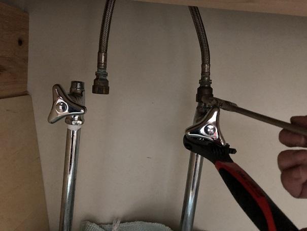 止水栓からキッチン水栓のホースを外すところ