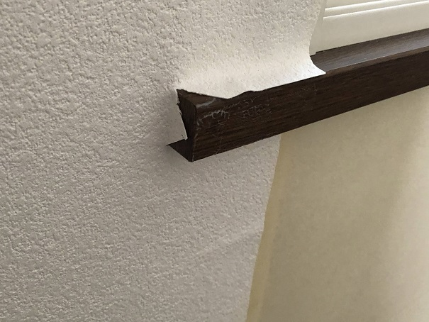 壁の窓まわりの出っ張りを回避して壁紙を自分で貼る様子