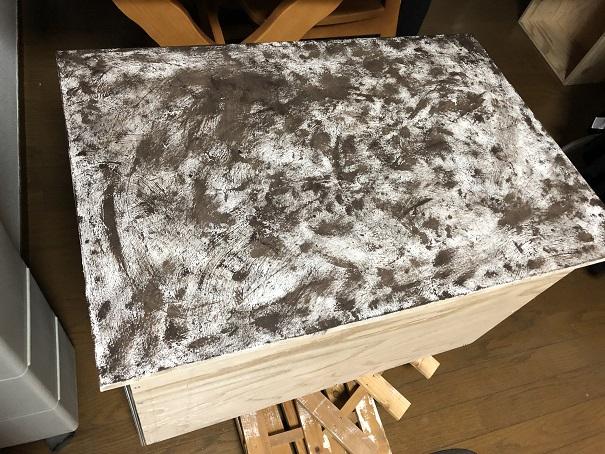 キッチンシンク下に設置した引き出し収納 無塗装の前板にデコボコベースを塗って、茶色い塗料を重ねたところ