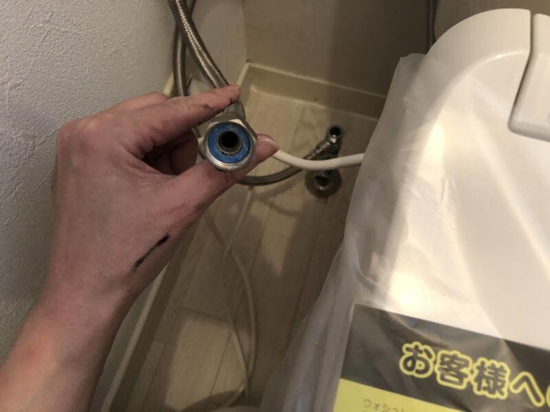 給水ホースのパッキンをセットしているところ